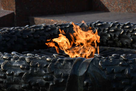 Burning fire closeup of eternal flame of monument in Odessa city park of Ukraine. Fire flames inside bronze monument