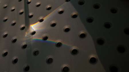 Sun flare of rainbow spectrum light on dotted surface with abstract shadows. Circle hole pattern background