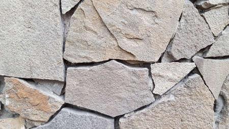 Rough stone mosaic textured background. Brickwork backdrop. Stone masonry wall surface closeup Banco de Imagens