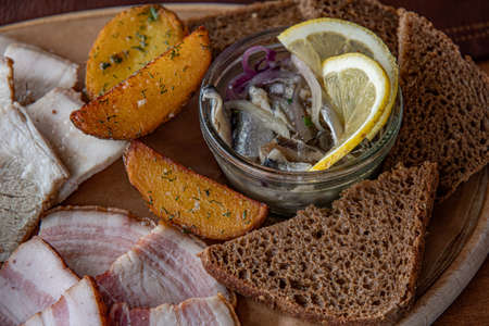 Bacon and pork fat served with fried potatoes. Slices of homemade roasted potatoes with dark bread toasts and salty anchovies with lemon Stockfoto