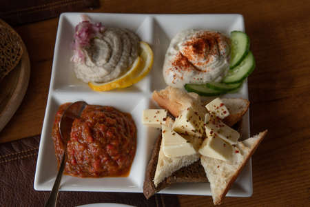 White crockery plate with mezze tasting set of assorted pate pastes and appetizers made from mashed vegetables. Bread toasts and butter pieces with spicy seasonings. Traditional Mediterranean cuisine