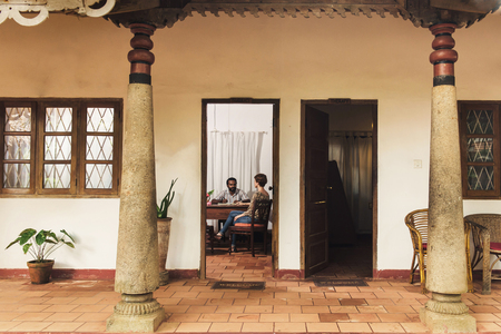 Caucasian woman consulting a doctor before Ayurveda treatment in India. Kerala. View from outside though the door