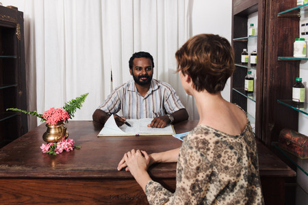 Caucasian woman consulting a doctor before Ayurveda treatment in India. Kerala. Patient from the back. Stock Photo