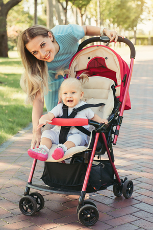 fastened: Young mother talking to smiling baby in pink stroller. Parents walking outdoors with child in summer pram.