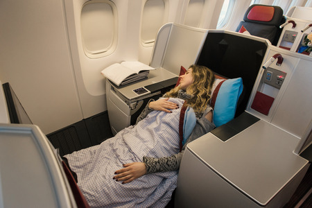 Woman passenger sleeping at the business class of airplane in comfortable single seat. Flight at first class plane Archivio Fotografico