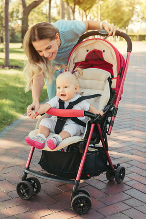 sidewalk talk: Young mother talking to smiling baby in pink stroller. Parents walking outdoors with child in summer pram.