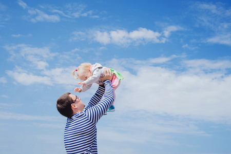 Father tossing little daughter to the air over the sky. Family having fun outdoors and best moments together. Stock Photo