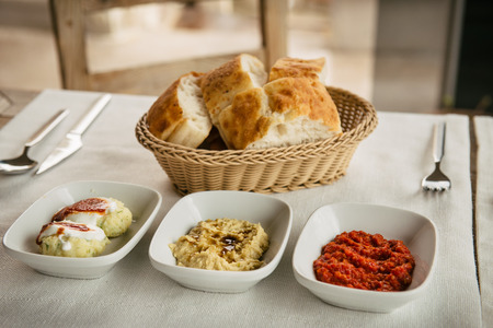 Mezze is selection of small dishes served in the Near East, and parts of Central Asia. In Turkey meze is served at the beginning of multi-course meals. Table served with hummus, Antep Ezmesi and bread