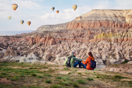 Couple of travelers enjoying landscape of Red valley in Cappadocia near Goreme on the sunset. Man and woman sitting on the cliff of mountains in Turkey.