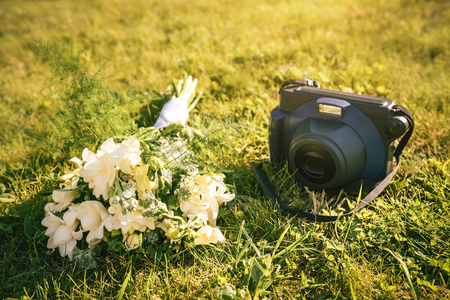 Retro camera and wedding bouquet on green grass. Moment photo for celebration