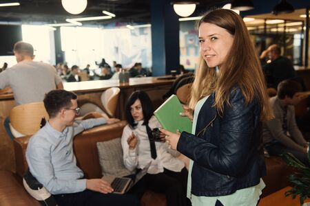 Smiling woman looking to the camera during business conversation in office. Business people in co-working