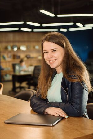 Smiling freelancer woman working at co-working or creative space, sitting near laptop over group of people