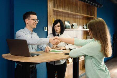 Handshake of happy business people and company staff in modern office celebrating success, representing company.