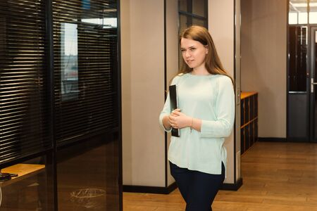 Smiling freelancer woman working at co-working or creative space, standing with laptop on the corridor of office