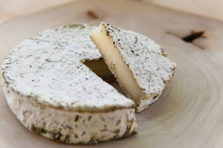Craft organic cheese in herbs, handcrafted goat cheese, appetizer on wooden table.