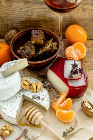 Rustic cheese platter with camembert, brie, gouda on wooden table, variety of farm dairy appetizers with mandarins and wine