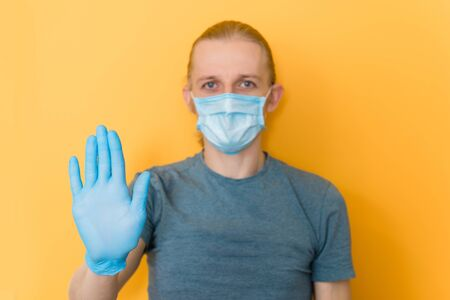 Stay at home, be safe during coronavirus pandemic. Man in rubber gloves and mask over orange background