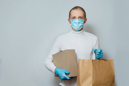 Man holding paper bag, box with food, or goods in medical gloves and protective mask, copy space. Safe grocery delivery, young courier during coronavirus quarantine.