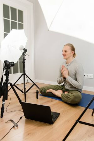 Online yoga meditation, webinar e-learning at home, video conferencing, distant trainings, teaching using Internet and technologies. Wloger streaming. Camera close-up, blurred teacher, copy space. Archivio Fotografico