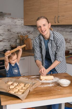 Father and child cooking on the kitchen with fun. Family baking cinnabons