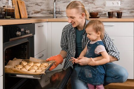 Father and kid waiting for freshly baked buns bread, cinnabons or pastry near the oven happy time together at home cooking