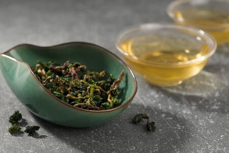 Dry tea leaves and hot drink in asian style cups. Oolong chinese tea in cha he