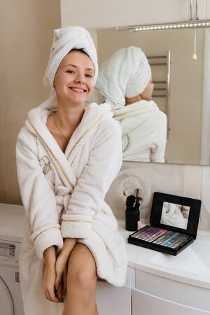 Woman doing herself makeup at home after taking shower. Self skin care procedure Archivio Fotografico