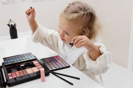 Toddler girl doing herself makeup with mamas cosmetics pretending grownup. Applying eyeshadows. Child in the bathrobe at home
