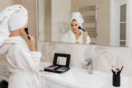 Woman doing herself makeup at home after taking shower. Self skin care procedure. Beautiful lady reflected at the mirror Archivio Fotografico