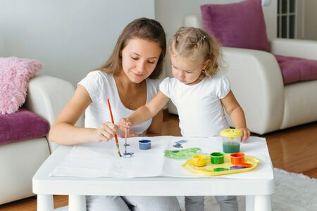 Mother and toddler daughter painting at home. Happy creative family with child spending time together with fun and joy. Learning colours