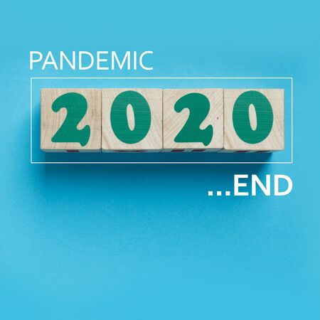 The End of Pandemic in 2020 in wooden blocks on square blue background with copy space. Covid-19 quarantine is over