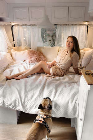 Sexy relaxed woman in trailer bed in the morning with dog, while traveling and camping.