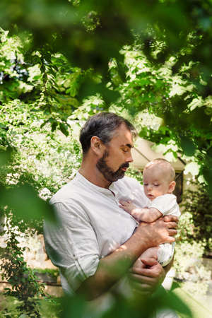 Father with baby boy in green leafs filling nice and tender, fatherhood. Cute little son on dads laps