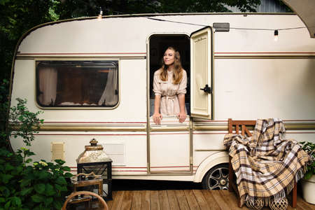 Camping and travelling . Happy person relaxing outdoors near trailer. Woman is ready for road trip