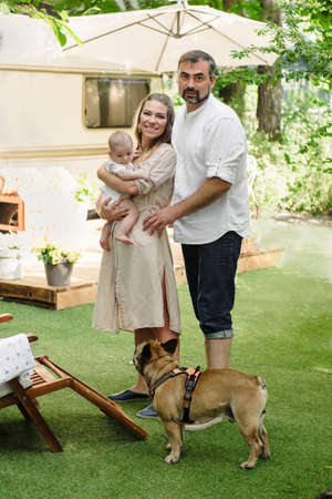 Family with baby and dog spending happy time together near trailer outside on deck chair, traveling lifestyle with camper