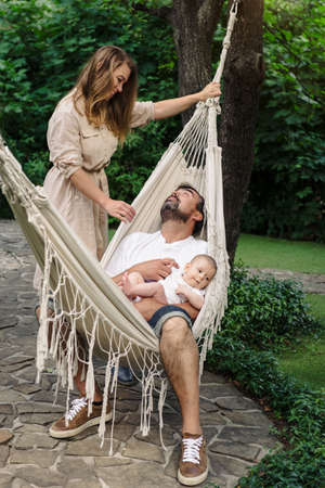 Family with baby boy in hammock filling nice and tender, fatherhood. Cute little son on dads laps Archivio Fotografico