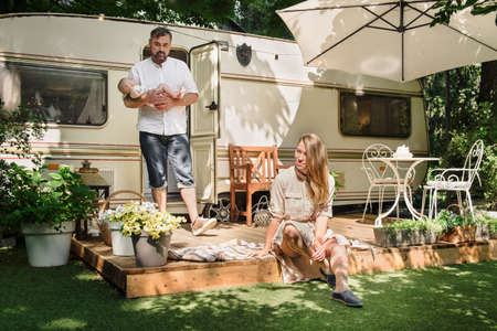 Family with baby spending happy time together near trailer outdoors, traveling lifestyle with camper Archivio Fotografico