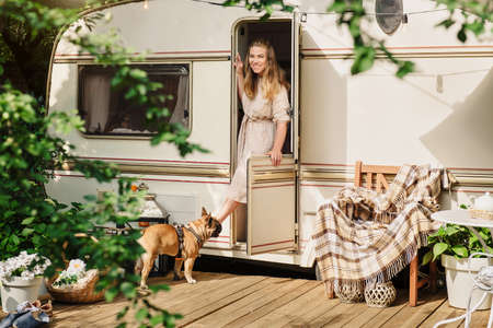 Camping and travelling . Happy person relaxing outdoors near trailer. Woman with dog is ready for road trip, Cozy sunny morning