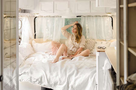 Sexy relaxed woman in trailer bed in the morning, while traveling and camping.