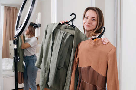 Female Blogger Recording Vlog Video on smartphone At Home Online Influencer On near wardrobe choosing clothes, earthly look. Stylist on-line consulting Dress or shirt.