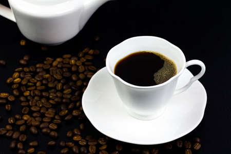 Black coffee in white ceramic cup and coffee beans on black wooden background, dark tone. Imagens
