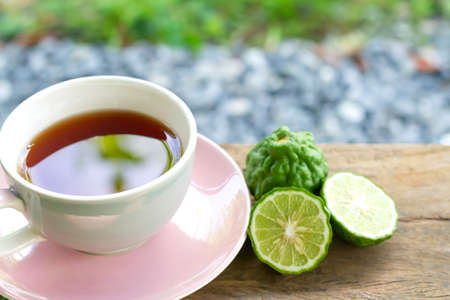 Bergamot tea or Earl Grey tea in white cup and fresh bergamot fruit with sliced on wooden table and blur background.