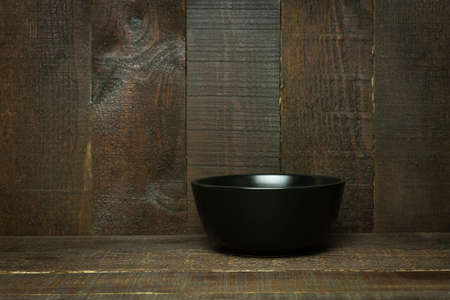 Empty Black bowl ceramic on wooden background for graphic design.