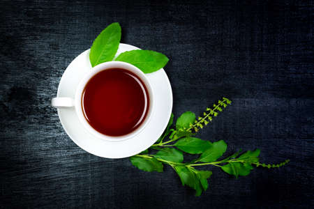 Tulsi or holy basil tea in white cup with fresh tulsi branch and leaf on black wooden background, top view, darktone. Ayurvedic medicine in India.