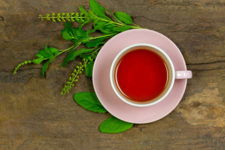 Tulsi or holy basil tea in ceramic cup with fresh tulsi branch on rustic wooden background top view. Ayurvedic medicine in India.