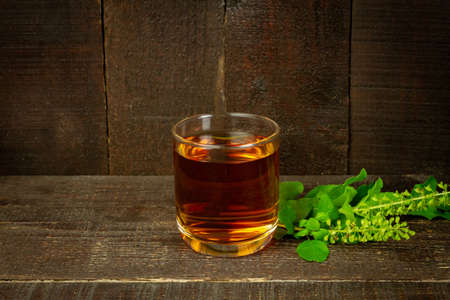 Tulsi or holy basil tea in transparent glass with fresh tulsi leaf on wooden background. Ayurvedic medicine in India.