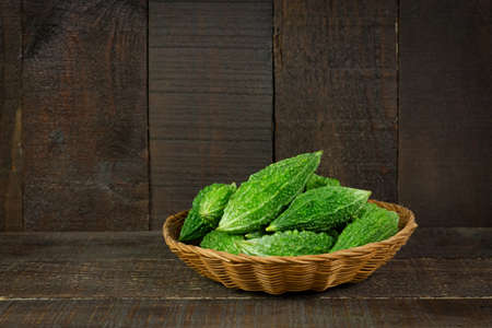 Bitter gourd or bitter melon in basket on wooden background. Scientific name is Momordica charantia. As a whole food and herbs for treating diseases. Stock Photo