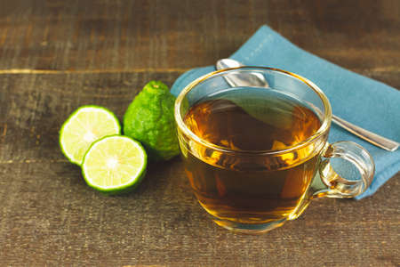 Bergamot tea or Earl Grey tea in transparent cup and fresh bergamot fruit with sliced on wooden table. Stock Photo