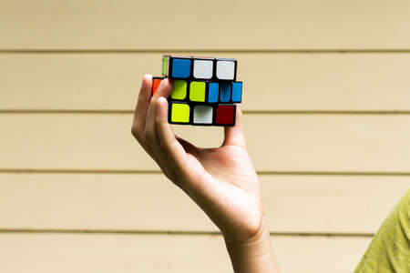 SAMUT-SAKHON, THAILAND - MAY 09, 2021 : Hands of young girl showing the Rubik's Cube puzzle on cream color background, Illustrative editorial.