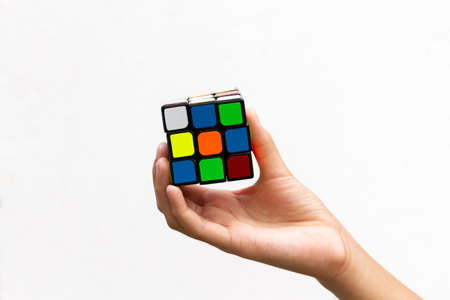 SAMUT-SAKHON, THAILAND - MAY 09, 2021 : Hands of young girl showing the Rubik's Cube puzzle on white background, Illustrative editorial.